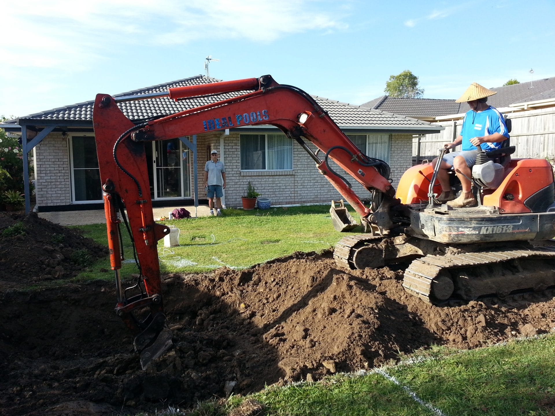 An excavator digging a hole for a pool at a home on the Gold Coast
